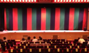 開演前の劇場。幕があがって最初にお客さんの目に入るのは背景幕です。